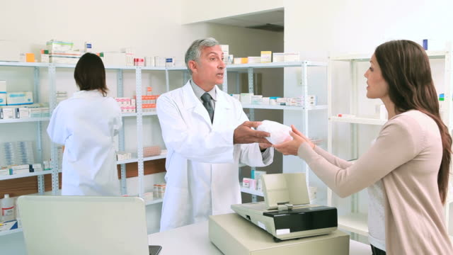 Pharmacist giving a bag of pills to a female client
