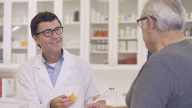 pharmacist giving advice to senior man - moving image stock videos & royalty-free footage