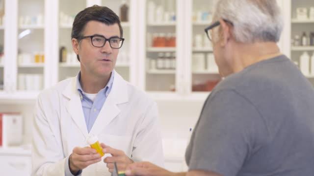 pharmacist giving advice to senior man - prescription medicine bottles stock videos & royalty-free footage
