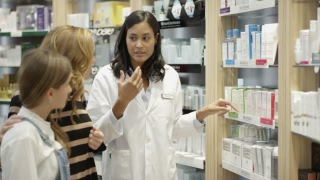 vídeos de stock e filmes b-roll de pharmacist guiding customers in buying medicines - farmácia