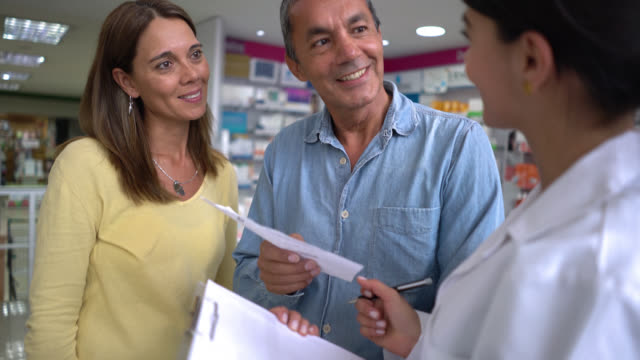 Pharmacist helping a couple at a drugstore
