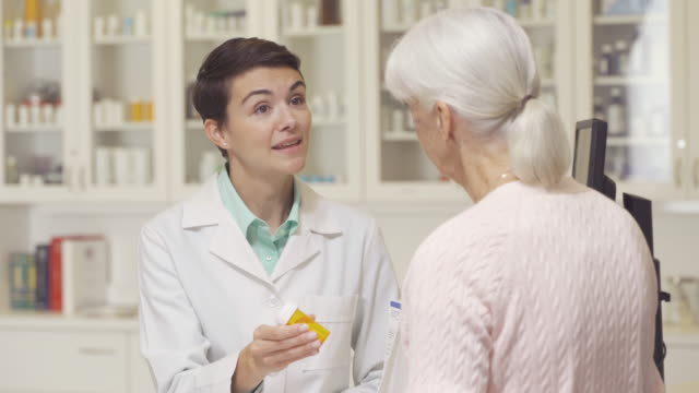pharmacist helping senior woman - apotheke stock-videos und b-roll-filmmaterial