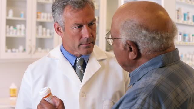 CU TU Pharmacist Holding Prescription Bottle, Talking to Senior Customer / Richmond, Virginia, USA