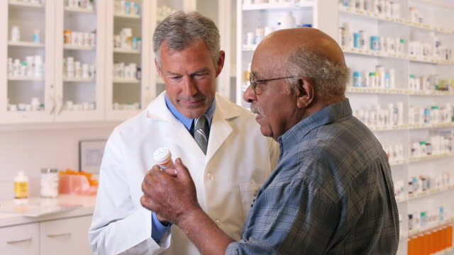 MS Pharmacist Holding Prescription Bottle, Talking to Senior Customer / Richmond, Virginia, USA