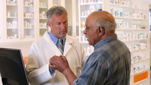 MS PAN Pharmacist Holding Prescription Bottle, Talking to Senior Customer / Richmond, Virginia, USA