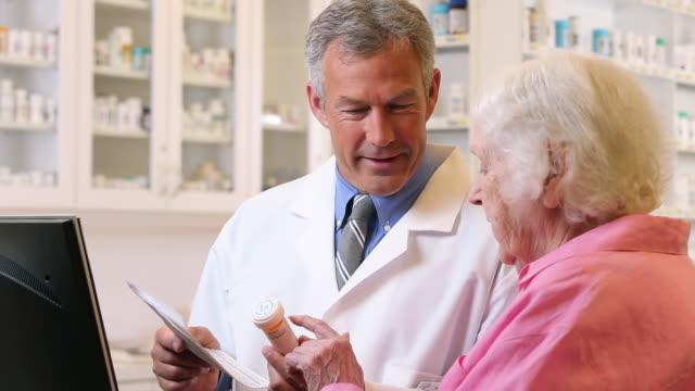 ms pan pharmacist holding prescription bottle, talking to senior customer / richmond, virginia, usa - apotheke stock-videos und b-roll-filmmaterial