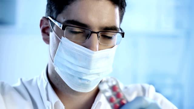 Pharmacist holding red pill
