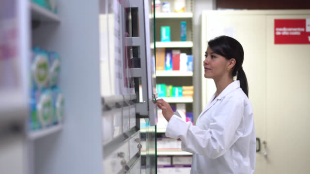 pharmacist opening the cabinet and taking out a prescription drug - pharmacy stock videos & royalty-free footage