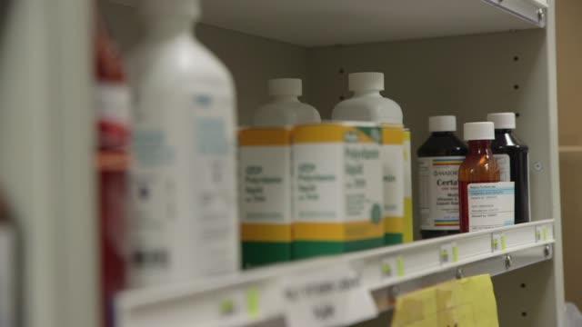 pharmacist picks up bottle of valporic acid in pharmacy at harborview hospital in seattle. - prescription medicine bottles stock videos & royalty-free footage