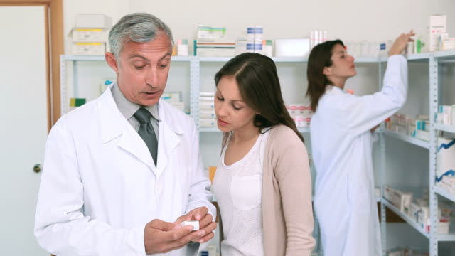 vídeos de stock e filmes b-roll de pharmacist pointing at a flask of pills in front of a customer - cliente