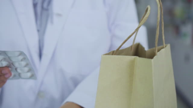 pharmacist puts the medicine in the bag for customer,slow motion - rx stock videos & royalty-free footage