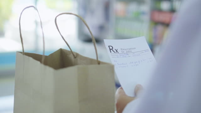 pharmacist puts the medicine in the bag for customer,slow motion - pharmacy stock videos & royalty-free footage