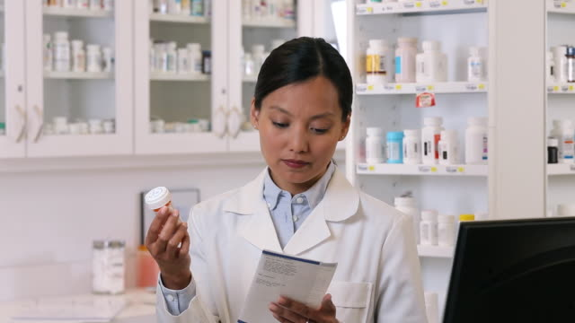 ms pan pharmacist reading label of medicine bottle to fill prescription / richmond, virginia, usa - prescription medicine stock-videos und b-roll-filmmaterial