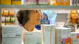Pharmacist searching for medication on shelves