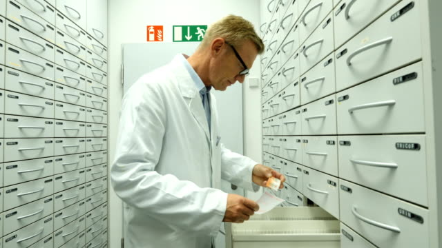 pharmacist searching medicine in filling cabinets - compartment stock videos & royalty-free footage