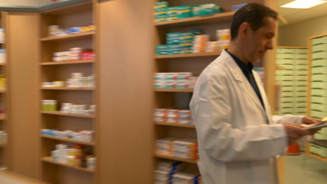 Pharmacist Searching Medicines For Senior Man