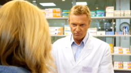 Pharmacist selling medicine to customer in store