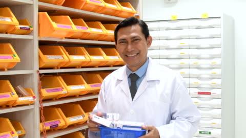 vidéos et rushes de pharmacien, souriant à la caméra de médicaments - cadrage à la taille