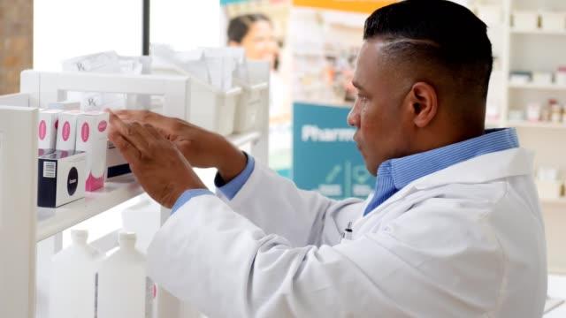 pharmacist stocks shelves in pharmacy - shelf stock videos & royalty-free footage