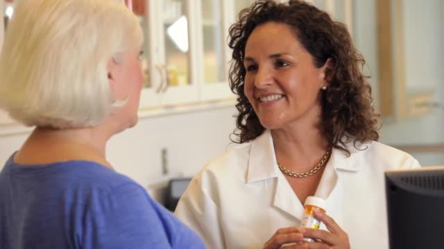 """vídeos y material grabado en eventos de stock de """"pharmacist talking to a senior customer about a prescription /richmond,virginia, usa"""" - droga"""