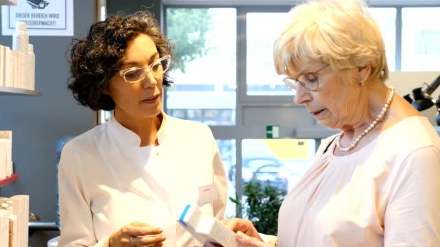 vídeos y material grabado en eventos de stock de farmacéutico, hablar al cliente senior en farmacia - receta instrucciones