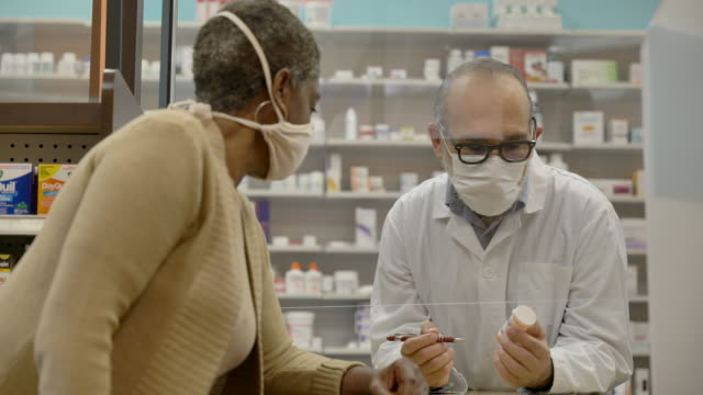 pharmacist wearing a mask - fatcamera stock videos & royalty-free footage