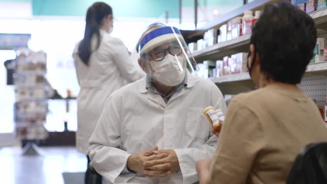 pharmacist wearing a mask - prescription medicine stock videos & royalty-free footage