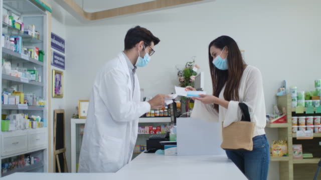 vídeos de stock e filmes b-roll de pharmacist wearing a surgical mask tells the male patient who wears a surgical mask how to use his medicine - farmácia