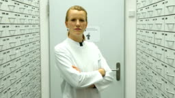 Pharmacist with arms crossed in storage room
