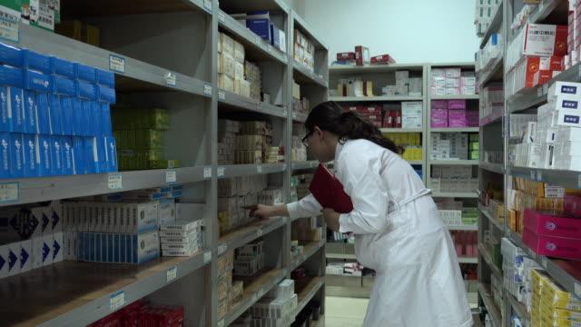 vídeos y material grabado en eventos de stock de pharmacist working in pharmacy - cabello recogido