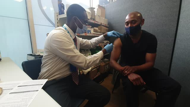 pharmacy manager osei akoto administers the first dose of the oxford-astrazeneca covid vaccine to brian dayle at the nhs vaccine centre at day lewis... - brian dayle coronavirus stock videos & royalty-free footage