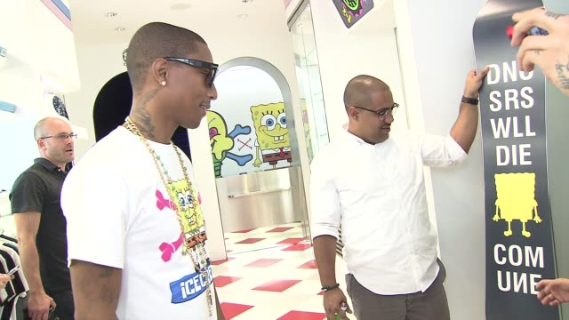 pharrell williams checks out a customized snowboard at nickelodeon and pharrell williams debut spongebob x icecream brand capsule collection on... - nickelodeon stock videos & royalty-free footage
