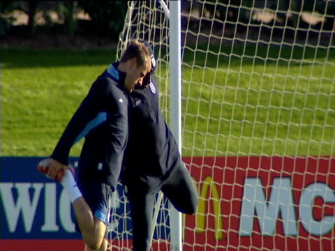 vidéos et rushes de phil neville and sol campbell balance on each other as they stretch quadriceps during england football training session 15 oct 03 - membres du corps humain