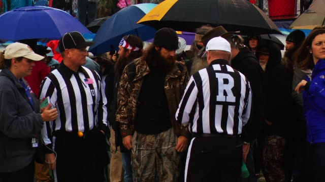 vídeos de stock, filmes e b-roll de phil willie and jase roberston of 'duck dynasty' speak with refferees at the 2014 duck commander bowl in celebrity sighting in shreveport - liga esportiva