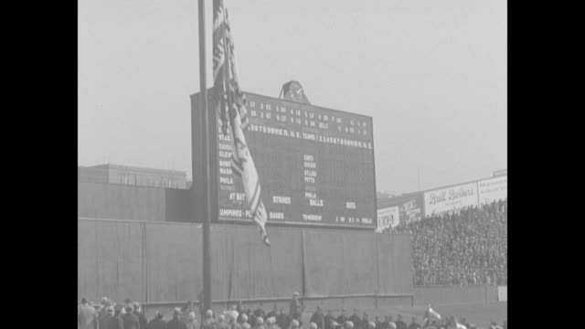Philadelphia Athletics and New York Yankees parade down field at Yankee Stadium in front of packed stands / teams are grouped around flagpole as...
