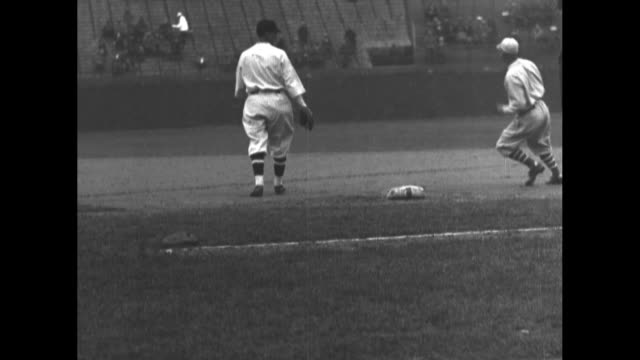 philadelphia athletics player gets a hit runs to base during game against washington senators at griffith stadium / another philadelphia player hits... - baseballspieler stock-videos und b-roll-filmmaterial