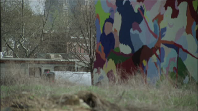 philadelphia city hall stands in the distance beyond a building with an abstract mural. - male likeness stock videos & royalty-free footage