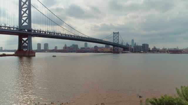 フィラデルフィア・ダウンタウンベンジャミン・フランクリン橋とデラウェア川の遠隔ビュー。カメラの動きが昇天した空中ドローンビデオ。 - ベンフランクリン橋点の映像素材/bロール