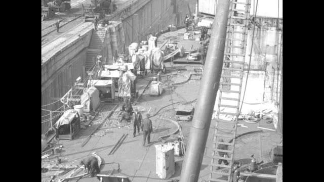 [philadelphia pa] dry dock with two cranes overhead the uss oklahoma / elevated view of workers on the ship's deck / a welder works with an acetylene... - 1920 1929 stock videos & royalty-free footage