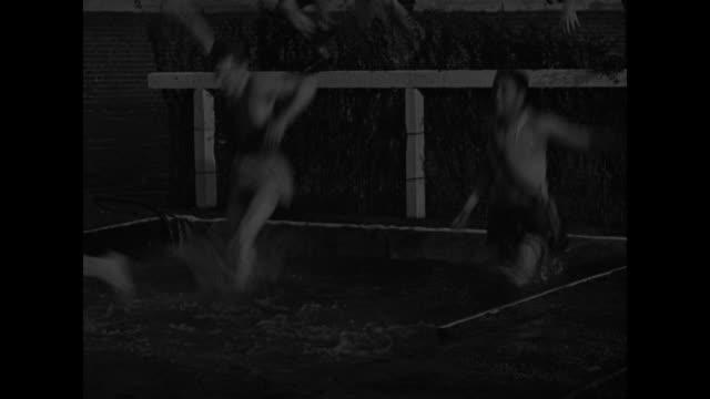 the Penn Relays' 3000 meter steeplechase starts with bang of starter pistol men jump barricade across water barrier / muddy Alfred Knapp wins Penn...