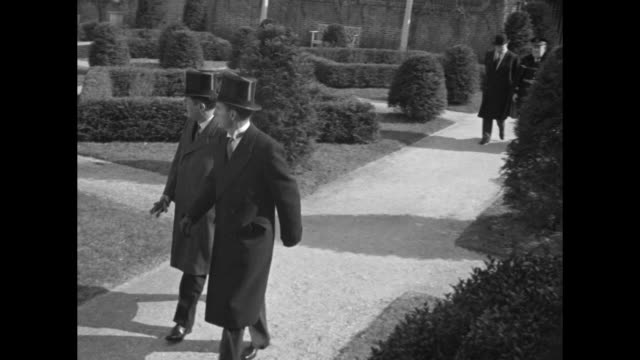 vídeos y material grabado en eventos de stock de philanthropist john d rockefeller iii and virginia governor james price walking through grounds of governor's palace in colonial williamsburg, va /... - sombrero de copa