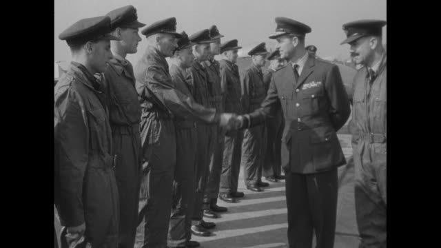 Philip Duke of Edinburgh approaches with officers as he walks on airfield during military review of British Air Force unit planes and pilots stand at...