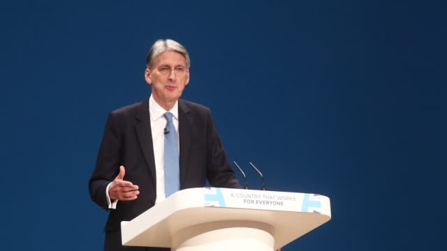 Philip Hammond UK chancellor of the exchequer speaks as photographers work in the foreground during the second day of the Conservative party's annual...