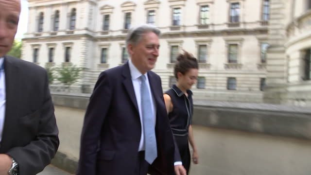 philip hammond walking in whitehall on the day boris johnson became prime minister and he resigned from cabinet as chancellor of the exchequer - フィリップ ハモンド点の映像素材/bロール