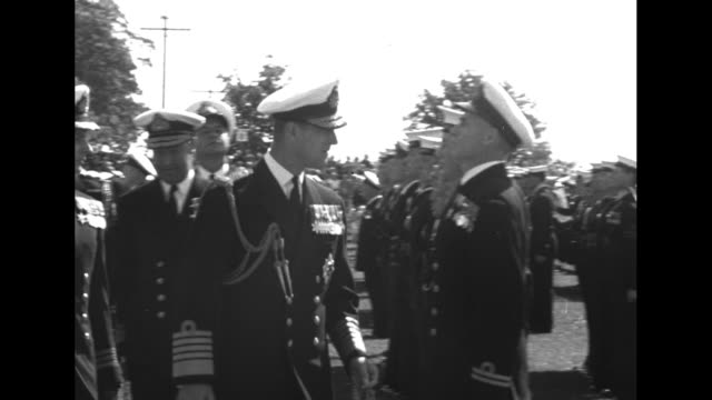 vidéos et rushes de philip in navy uniform accompanied by officers canadian navy walks along front of formation of naval personnel inspecting them / at airport in rivers... - marine