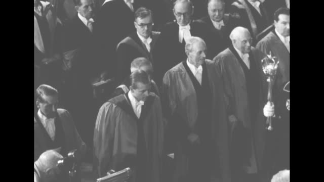philip standing on dais in chancellor's robe touches man with his cap / from behind man another man places academic hood over his head onto shoulders... - chancellor stock videos and b-roll footage