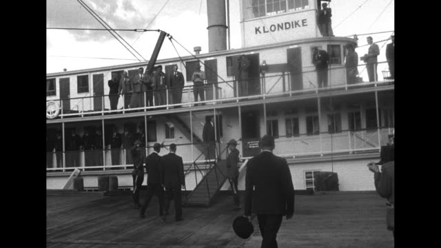 philip walks across pier with officials towards paddleboat / he walks up gangway to boat / shot from below of word klondike painted on side of... - klondike river stock videos and b-roll footage