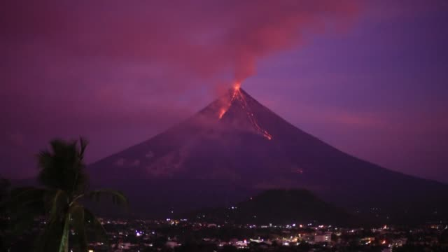 stockvideo's en b-roll-footage met philippine volcano mayon appears purple during sunrise as it has spewed millions of tonnes of ash rocks lava and debris in less than three weeks and... - active volcano