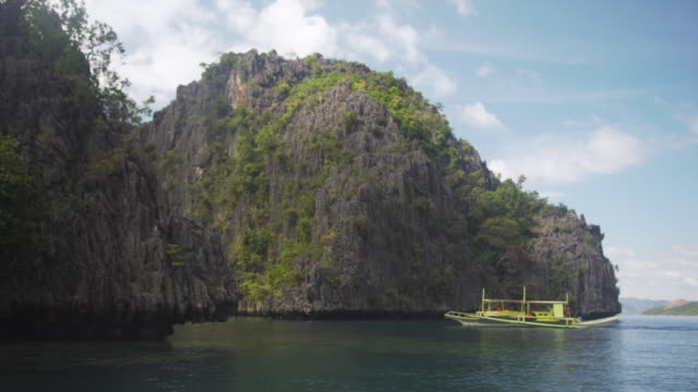 philippines iconic landscape with traditional boat with outriggers and islands with cliff - ウォータースポーツ点の映像素材/bロール