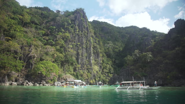 philippines iconic landscape with traditional boat with outriggers and islands with cliff - filippine video stock e b–roll